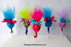 TROLLS PARTY FAVOR SUCKERS Materials: Tulle Ribbon Small flowers Suckers Scissors Glue Directions: cut tulle into rectangles (measure to make sure it is the desired size) make appx 3 squares (more if desire a solid look) cut small slit in the center of your tulle rectangles Poke your sucker through your tulle pieces Tie tulle with a ribbon at the top of your sucker glue a small flower to the center of the bow FIND MORE FUN TROLL ITEMS HERE or find more PARTY FAVORS HERE This post contains…
