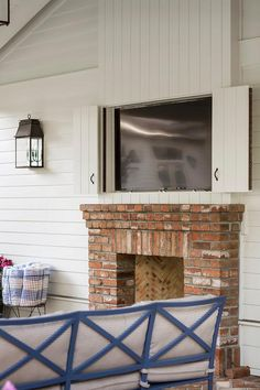 Chic covered patio features concealed flat panel television hidden behind sliding folding doors placed above a red brick outdoor fireplace.