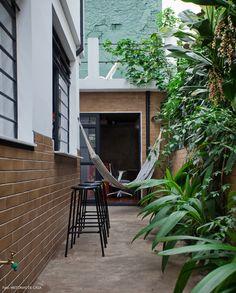 mesmo em um terreno estreito, essa casa conseguiu aproveitar bem as áreas externas, como esse jardim lateral cheio de plantas