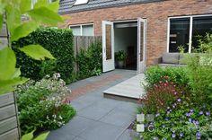Een kleine tuin in Vleuten van 40 m2 toont groter door de lange lijn van klinkers vanuit de openslaande deuren. De beplanting is kleurrijk en weelderig.