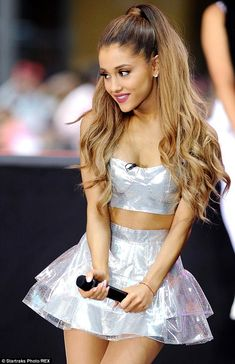Ariana Grande performs in metallic mini skirt and bralet #dailymail