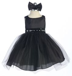 Black Baby Dress With Rhinestone And Tulle Skirt: This gorgeous rhinestone black baby dress features a taffeta bodice and tulle skirt with additional netting underneath for a full volume ballerina skirt look. The waistline is embellished with elegant rhinestone jewels, delicate beading, and iridescent sequin. Your baby will be the belle of the ball in this exquisite black baby dress.