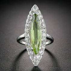 Vintage Marquise Peridot Ring with Diamonds. Just shy of 1 and 1/4 inch long and lovely, this sleek and slender dinner ring glistens front and center with an elongated navette shape, lime green peridot enveloped in a glittering halo of small old mine-cut diamonds. Hand fabricated in platinum, circa 1920s, this is a truly singular and sensational Art Deco jewel.