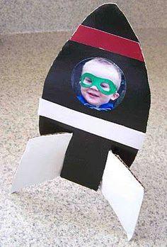 Nave espacial de cartón con foto del niño en el interior.