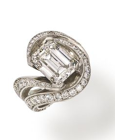 A diamond solitaire ring, Donovan Seamans centering a cut-cornered rectangular-cut diamond, weighing 6.00 carats, within a round brilliant-cut diamond scrolling surround, shoulders and heavy platinum mount; signed D for Donovan Seamans; remaining diamonds weighing approximately: 1.60 carats total; mounted in platinum