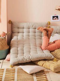 Un matelas de sol terminé par des pompons jaune moutarde crée une zone de repos, de jeu et de lecture pensées pour votre enfant
