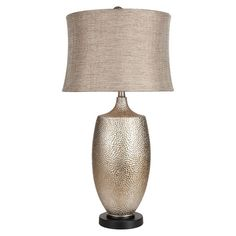 Cast a stylish glow over your bedside or favorite reading nook with this silver leaf-finished table lamp, featuring a hammered vase-shaped base and cinched s...