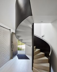 The main entrance opens into a hallway where a spiralling staircase ascends through a skylit double-height space to connect with a study and master bedroom on the first floor.