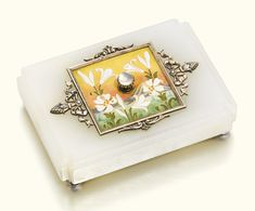 A Fabergé silver-gilt, enamel and hardstone bellpush, workmaster Michael Perchin, St Petersburg, 1899-1903. In Japonesque taste, the moonstone pushpiece centred within an enamel plaque painted en plein with white lilies at sunrise over Mount Fuji, the border with leaf scrolls, ribbons and fir cones, the rectangular white chalcedony base with cut corners and ogee edge.