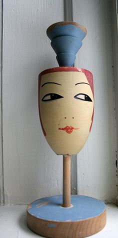 The original description of this hat stand said 1930s, but knowing hat shapes and lipstick styles, i'm more inclined to guess 1920s, because the lift at the top would hold a cloche's deep crown in just the right position to look super cute on this!