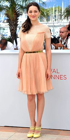MARION COTILLARD  Life's a peach for the French actress, who looks perfectly sweet in a Dior gown encircled with a slim gold belt, plus pastel yellow heels, for a Rust and Bone photo call.