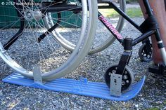 Plastic skis attached under the wheelchair