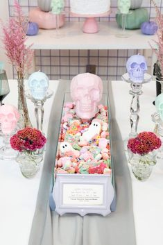 Create this easy DIY sweet treat centerpiece for a Pastel Skull Themed Halloween Party, using a terrarium! Get the details and more party decor, place setting, and dessert table ideas for this party now at fernandmaple.com!