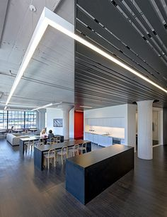 Linear lighting elements integrated into the slatted system break free in places where the raw original ceiling is exposed, connecting old with new.