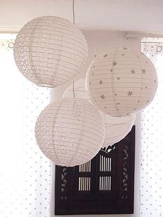 Un groupe de lanternes chinoises, une seule est au bout de l'ampoule, les autres sont punaisées au bout d'un fil de pêche