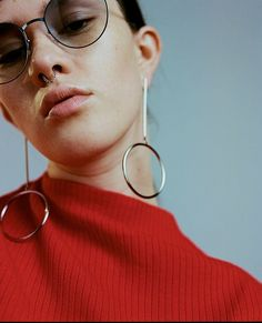 funky earrings and a red ribbed sweater