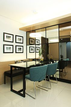 The dining area features a mirrored accent wall%u2014with a combination of plain and bronze mirrors. This design element not only livens up this part of the unit, it also creates an illusion of space. To keep the dining nook comfy and efficient, a bench seating was added on the left side of the table. This is ideal if the future occupants love having friends over for get-togethers. Meanwhile, the blue chairs add a touch of color and keep the dominantly neutral space from being boring.