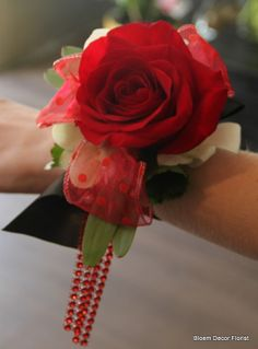 Wrist corsage with open red rose, white dendrobium orchids, on galax and protea leaf with red dangling jewel accents.