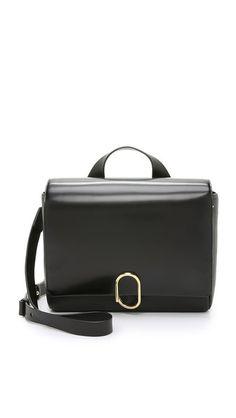 A pebbled leather 3.1 Phillip Lim messenger bag with a magnetic back pocket. A brass clasp fastens the fold-over top. Single handle and optional, adjustable shoulder strap. -  3.1 Phillip Lim Alix Messenger