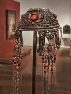 Married Woman's Skullcap Headdress and attached Temple Pendants. Mongolia Khalka region, Qing Dynasty, mid-19th century. Silver, coral and turquoise.
