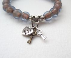 Stretch Bracelet, in pale blue glass beads, lined with shimmering copper, accented with Tibetan silver and with a gorgeous bail carrying two tiny skeleton keys - so cute! One of a Kind - great with denim!  Medium chunky and well-funky bracelet. NB: The earrings shown are yours free when you add this bracelet to your cart today! Beads are approx 8mm but as these are all handmade, there are slight variances which I think makes this look more handmade: but Ive spent a while matching the…