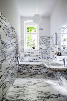 A dramatic, marble-clad bathroom is topped off and balanced by a pristine white stretch of wall and ceiling. Photo via In LIFE.