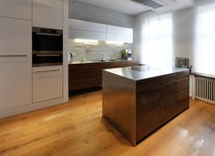 American walnut kitchen with industrial flair thanks to the simple outlining, indirect lighting and steel cabinets. Private kitchen in Hamburg, Germany