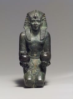 Kneeling statuette of King Amasis  Period: Late Period, Saite Dynasty: Dynasty 26 Reign: reign of Amasis Date: 570–526 B.C. Geography: Egypt Medium: Bronze, precious metal inlay and leaf