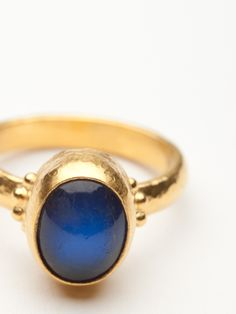 A majestic cabochon blue moonstone is the focal point of this ring.  The oval shaped stone has been bezel in 24kt hand hammered yellow gold. Small granulation details have been added around the stone display at the shank.  Size 6.25.