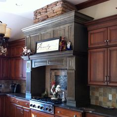 Amazing two tone kitchen. Green hood cherry glazed cabinets and exterior stone over cook top to hide exhaust.