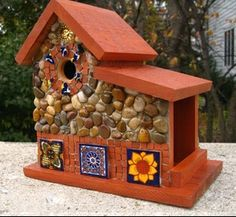 "South of The Border Cedar Wren house with side feeder.  Mexican tiles,  mini terra cotta tiles, stones and river rock collected from the shores of Lake Michigan, local rivers and from creek beds. Red maple stained roof and base. Suitable for outdoor or indoor décor. 11 1/2"" high  x 7"" deep x 11 3/4"" wide     1 1/8"" opening $169.00 plus shipping"