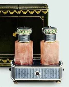 A PAIR OF BELLE EPOQUE ROSE QUARTZ, SAPPHIRE AND ENAMEL SCENT BOTTLES, BY CARTIER Cylindrical rose quartz bottles with blue guilloché enamel stoppers and cabochon sapphire finials to the rectangular-shaped holder , circa 1910, bottles 8.0cm high,  stopper with French assay marks for silver, with original green leather fitted maker's case.