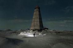 Slava walks to the old lighthouse near Khodovarikha