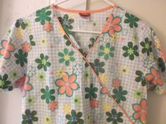 """Item Womens scrub top  Brand Dickies  Model Bright Floral Patten  of varying sizes with snowflake  like background Drawstring in  back  Size XS  Shoulder to Shoulder 15""""  Underarm to Underarm 18 1/2""""  Sleeve Length 7 3/4""""  Shoulder to Hem 26""""  ..."""