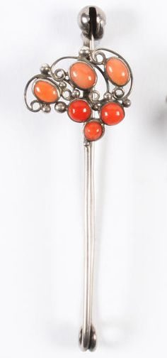 Dorrie Nossiter. Dorrie Nossiter. Coral kilt pin brooch. Unmarked, the mount of wire scrolls and beads collet set with various cabochons, to a plain bar with spherical terminal, 7.5 cm long. Sold by Bonhams.