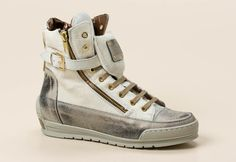 Ein klares modisches Statement setzt dieser edel wirkende Sneaker high von Candice Cooper. Goldfarbener Schmuck, Materialmix und die betonte, sportliche Sohle bestimmen die Aussage des 15cm hohen Sneakers. Grau-schwarzes Antik-Leder ist mit weißem Fell kombiniert. Weich ist der Besatz aus weißem Nubukleder am hinteren Schaftabschluss. Er ist feminin mit einem messingfarbenen Metallicleder gefüttert. Akzentvollen Glanz verleihen die goldfarbene Schließe, die Ösen, Nieten und Reißverschlüsse…
