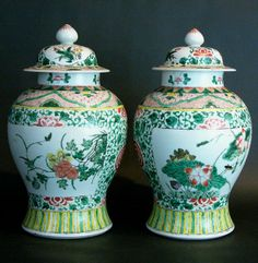 Pair of Chinese porcelain temple jars, bombed form with two lids, multicoloured floral decorations.