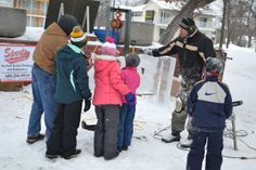 Visitors gather around an artist as he carves an ice sculpture at the 1st Annual Parks and Rec Winter Fest.