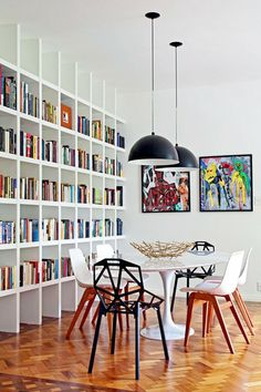 Colourful bookshelf mismatched chairs industrial light