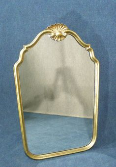 A beautiful vintage  gilt wood mirror  Lovely gilt frame with classic clam shell detail to top   Wonderful shaped frame  Hanging hooks to back, requires a chain  Measures approx   82 Cm's High   55 Cm's Wide