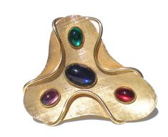 This wonderful vintage Napier brooch features four bezel stone glass stones in jewel tones. It has a textured abstract design with wire wrapping around front to back in a wavy style. Has minor wear, some discoloration to the metal in a few spots, everything can be seen on the photos. Measurements: 2 1/2 Diameter at widest point Please be sure to check out my shop for a *~HUGE~* variety of vintage jewelry that has FREE additional shipping.