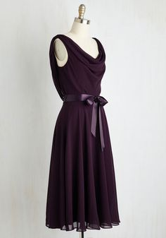 Your attention is always on this sweet things in life, like this flowing chiffon dress! Gracefully designed with a cowl neckline, a draping back detail, and a satiny ribbon sash, this deep purple dress is a feminine fashionista's delight!