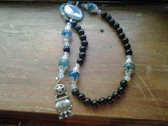 Midnight Magick - Obsidian beads and capped dragon vein agate form the strand. From it dangles a pewter cauldron. The center is a crow! $35