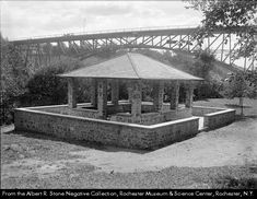 c1914 This pavilion was built in 1914 in Maplewood Park as a place for hikers to rest and enjoy the view. Horse-drawn wagons are seen crossing the bridge in the background.Rochester NY. This Maplewood Park Pavilion was built in 1914. It is surrounded by trees and provides a peaceful place for hikers to rest.
