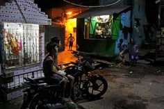 A family in their small slum residence, chatting and watching television at night, in the soon-to-be-destroyed Panditya Basti, on the outskirts of Kolkata. Photo by Souvid Datta