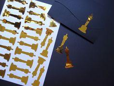 Cartela de adesivos formato estatueta do Oscar.  Altura do adesivo: 5cm (consulte outras opções de tamanho).  Medida da cartela: 20x14,5cm  Cada cartela contém: 26 unidades  Cor: dourado / ouro  Material: papel laminado adesivo com brilho (tipo contact)    IMPORTANTE: antes de entrar com o pedido...