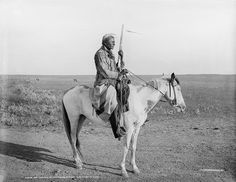 An Assiniboine Native American Indian named Rattlesnake on guard outside of the camp on the Fort Belknap Indian Reservation in 1879.