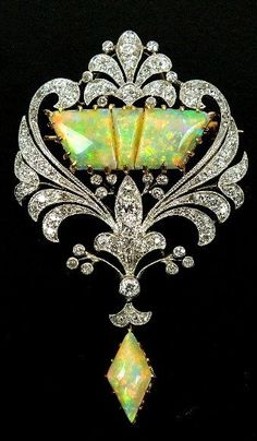 An early 20th century diamond and opal set brooch, designed as a three panel opal center within old cut diamond set openwork scroll border, all supporting opal drop, all claw, collet and pave set in yellow and white metal