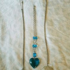 Heart necklaces 3 necklaces. First is a long necklace with a heart pendant that opens to reveal a clock. 2nd is silver colored and blue heart necklace. 3rd is a long silver heart necklace. Jewelry Necklaces