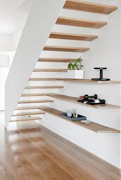 Holztreppe in weiß mit Regal, optische Verlängerung. Design.